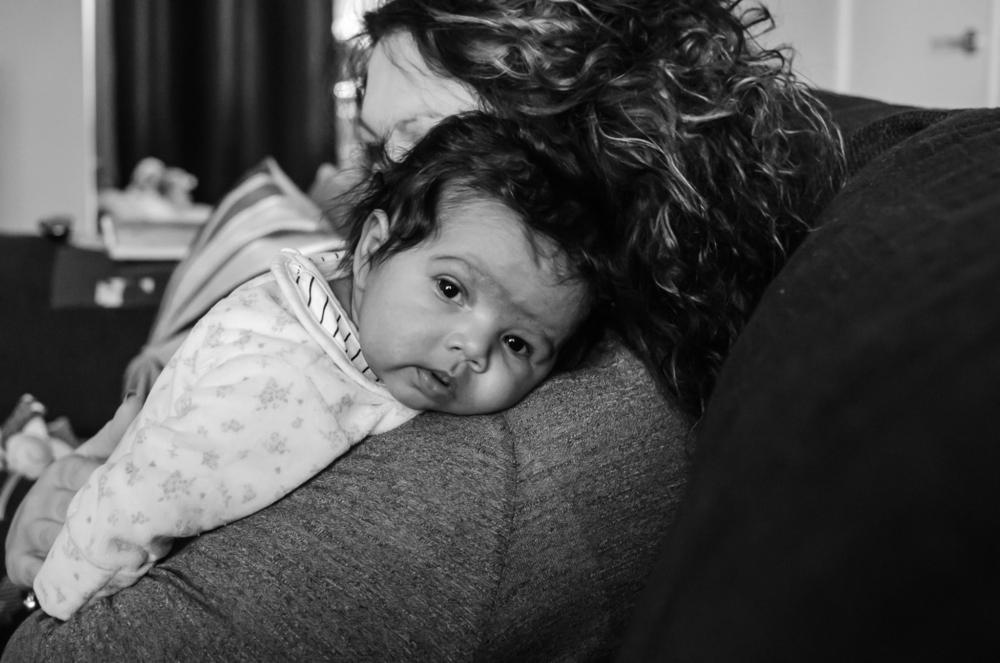 Baby girl lying on mum's shoulder