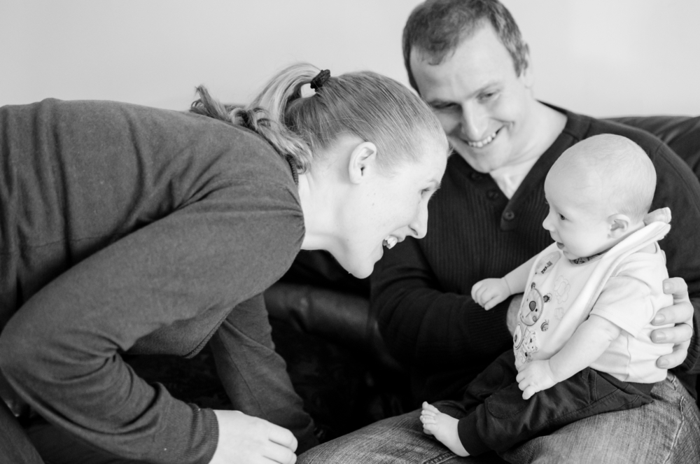 baby boy on dad's knee with mum laughing close to baby's face