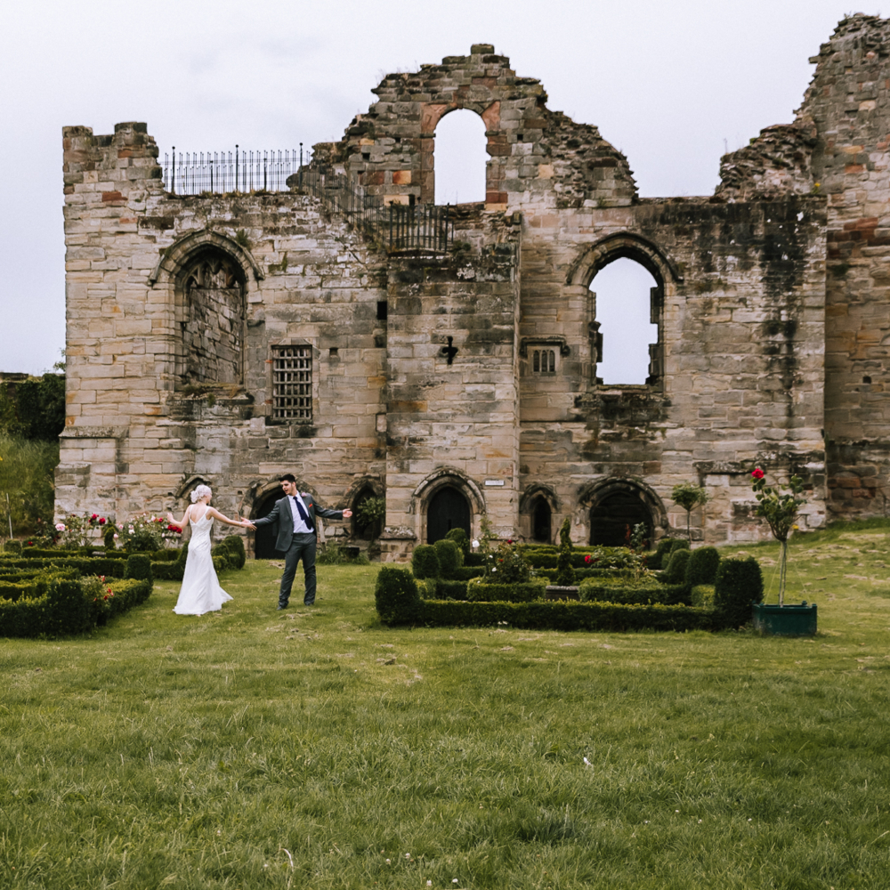 Bride and groom dancing on lawn in front of Tutbury castle