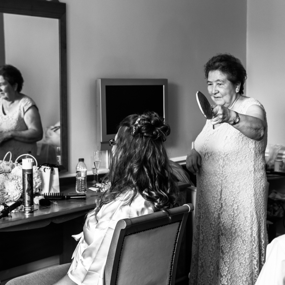 Bride sitting in front of the mirror with her mum holding a handheld mirror to show her the back of her hair