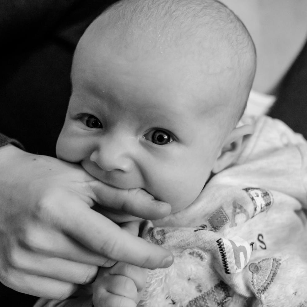 Baby boy biting mum's thumb