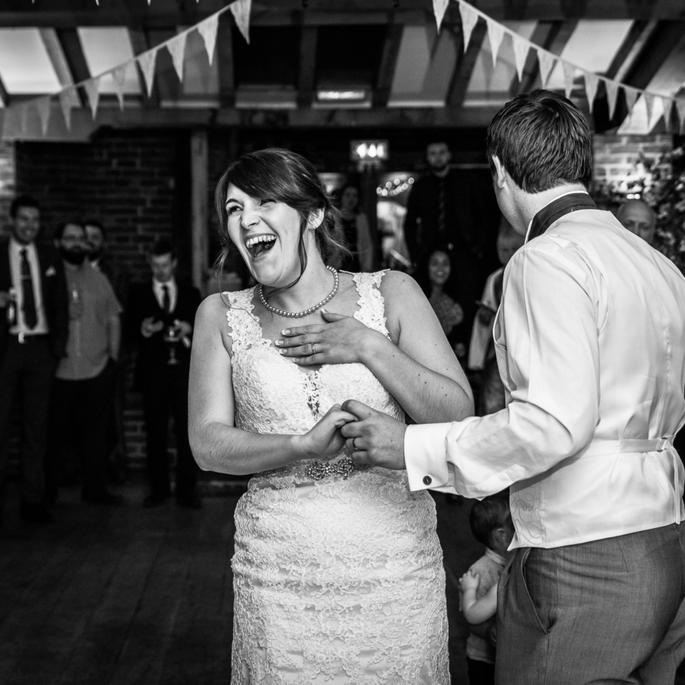 Bride dancing and laughing on dancefloor