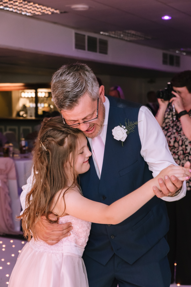 Groom dancing with his daughter on dance floor