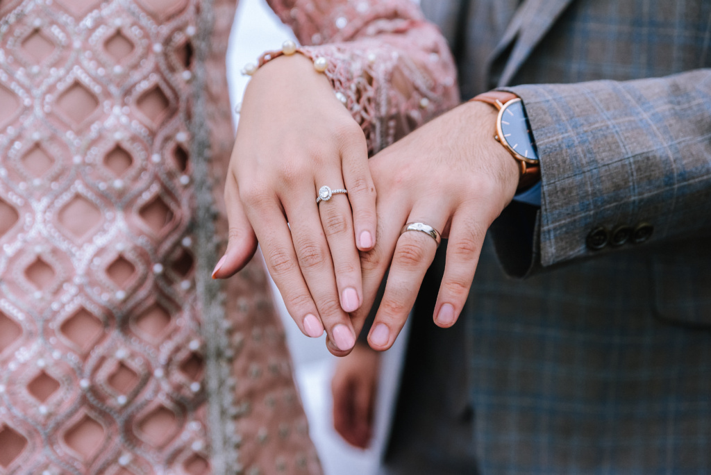 Asian girls hand with engagement ring on. Asian boy with engagement ring on